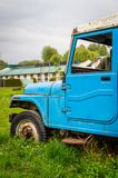 Abandoned vintage car blue lush green grass in college campus. Moody sky Royalty Free Stock Images