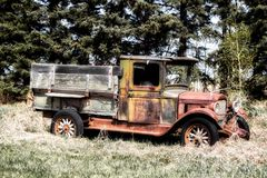 A vintage rusted truck. An abandoned vintage 1830s rusty truck with wood box in pretty good shape parked by a forest of trees Stock Photography