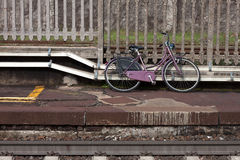 Abandoned violet bicycle along the tracks. Of a railway station Royalty Free Stock Photography