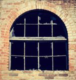 Abandoned warehouse facade detail with grungy broken window and broken glasses on a red brick wall. Dark inside, producing a scary atmosphere. Photo color royalty free stock image