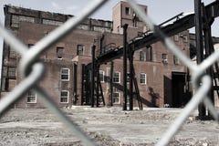 Abandoned warehouse through fence Stock Photos