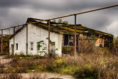 Abandoned warehouse and industrial buildings and buildings. Are covered with garbage and overgrown with bushes and grass Royalty Free Stock Images