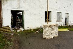 Abandoned warehouse and industrial buildings and buildings. Are covered with garbage and overgrown with bushes and grass Stock Image