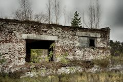Abandoned warehouse and industrial buildings and buildings. Are covered with garbage and overgrown with bushes and grass Stock Photo
