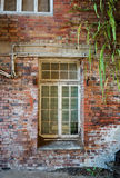 Abandoned warehouse wall. Warehouse abandoned due to recession showing window and textured bricks Stock Photography