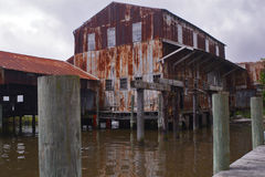 Abandoned Warehouse by Water. Old abandoned warehouse with dock and wooden dock by water on the Apalachicola River royalty free stock images