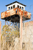 Abandoned watch-tower and prison fence wire barbs Stock Photography