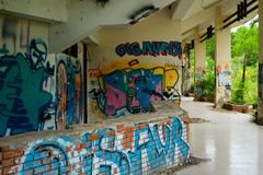 Abandoned water park, Hue. Old devastated building in old water park complex near to Vietnam town Hue. On the wall are color graffiti stock photography