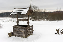 Abandoned well in winter. Abandoned well on a winter forest background Stock Image