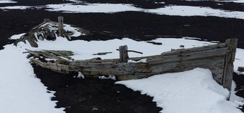 Abandoned whaler`s boat, Antarctica. A whaler`s boat abandoned and snow-filled on the black volcanic sand of Deception Island, Antarctica Royalty Free Stock Image