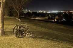 Abandoned wheel chair. On a hill at night. City lights in the background royalty free stock images
