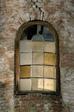 Abandoned Window. An old window with an arched top in an abandoned brick warehouse Royalty Free Stock Photography