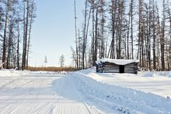 Abandoned winter hut on winter forest road. Abandoned snow-covered winter hut on winter forest road Stock Photography