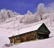 Abandoned wooden cottage in wintry view Royalty Free Stock Photos