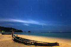 An abandoned wooden fishing boat on a sand beach at night Stock Images