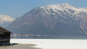 Abandoned wooden hut at lakeside, pan shot of majestic snowy mountain range. Stock footage stock footage