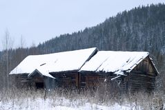 Abandoned wooden hut in the winter landscape stock photo