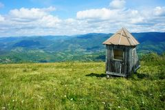 Abandoned wooden shed, small house, on a green meadow, blue horizon, mountains, Ukraine royalty free stock photo
