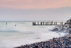 Abandoned wooden wharf in sea within sunrise.Gentle blue pink color of sky, blur waves Royalty Free Stock Image