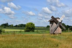 An abandoned wooden windmill in the vast green field near the forest. Barns and other constructions stand next stock images