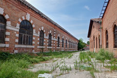 Abandoned workshops Arsenale, Venice, Italy. Abandoned workshops of the Arsenale, the ancient shipyard of the city of Venezia, Italy, with weed in the pavement Royalty Free Stock Photography