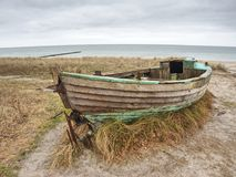 Abandoned wrecked boat stuck in sand. Old wooden boat on the sandy shore Royalty Free Stock Photos