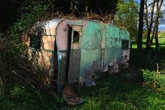Abandoned Wrecked retro caravan. Nature takes over. A wrecked abandoned retro style old pink and blue caravan left to nature to reclaim stock image