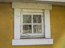 Abandoned yellow house with broken window Stock Images