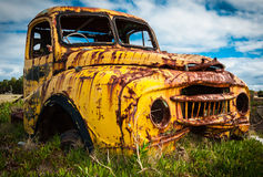 Abandoned yellow truck. Abandoned 1950's yellow truck wreck rusting in a field.  Variations of this subject available Stock Photo