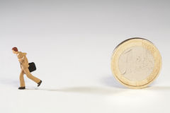 Abandoning The Euro. A miniature model businessman running away from an upright Euro coin with his briefcase Stock Photos