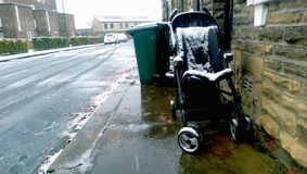 Abandonment. A photograph which captures a baby`s pram that has been abandoned outdoors overnight in the snow. This photo is the morning result Stock Photos
