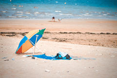 Abandonment,. An umbrella is abandoned to go to play the sea of the sea, one summer day Stock Image