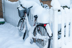 Abandonné avec la neige a couvert le vélo penché à une barrière devant a Images libres de droits