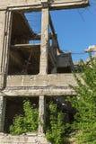 Abandonné détruit par l'explosion, bombardant et écossant le bâtiment détruit Trous des coquilles, traces des balles et attelle photos stock