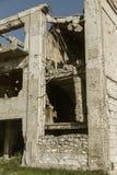 Abandonné détruit par l'explosion, bombardant et écossant le bâtiment détruit Trous des coquilles, traces des balles et attelle photo libre de droits