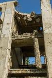 Abandonné détruit par l'explosion, bombardant et écossant le bâtiment détruit Trous des coquilles, traces des balles et attelle image stock