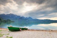 Abandonné pêchant le bateau de palette sur la banque du lac alps Lac morning rougeoyant par lumière du soleil Image stock