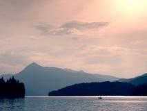 Abandonné pêchant le bateau de palette sur le lac alps Lac evening rougeoyant par lumière du soleil Image stock