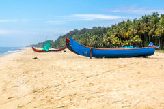 Abandonned artistic wooden canoe on a lonely beach. In India, Kerala royalty free stock photo