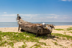 Abandonned artistic wooden canoe on a lonely beach. In India, Kerala stock images