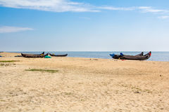 Abandonned artistic wooden canoe on a lonely beach. In India, Kerala royalty free stock photos