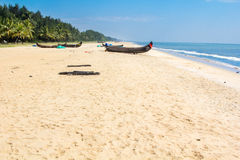 Abandonned artistic wooden canoe on a lonely beach. In India, Kerala royalty free stock image