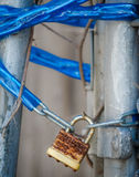 Abandoned padlock locks chain link gate with blue plastic covering Royalty Free Stock Image