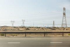 Abandonnez à coté de la route principale avec des courriers de l'électricité et des bâtiments de silhouette à l'arrière-plan chez Images stock