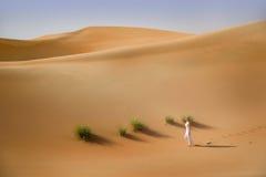 Abandonnez, des dunes de sable, les promenades de femme habillées par blanc Image stock