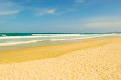 Abandonnez la plage de sable avec le ciel bleu et les vagues Photo libre de droits
