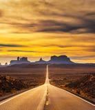 Abandonnez la route menant à la vallée de monument au coucher du soleil Photographie stock