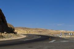 Abandonnez la route parmi les montagnes en pierre de Judean contre le bleu Photographie stock libre de droits