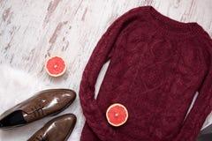 Abandonnez le chandail tricoté, chaussures de cuir verni brunes, moitiés coupées de pamplemousse Fond en bois Concept de mode Image stock