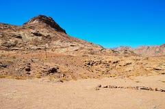 Abandonnez le paysage, montagnes de grès rouge, une plaine couverte de végétation rare de désert, un tronçon de route avec des po Image libre de droits